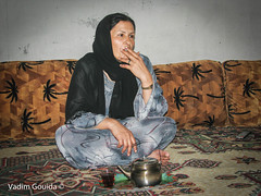 A beduin womanis smoking  in her concrete block house, Syria
