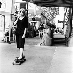 Multitasking (christait) Tags: blackandwhite bw woman canada calgary lady platform smoking hasselblad alberta yyc ctrain ilforddelta3200 500cm longboarder rodinal1100stand2hrs