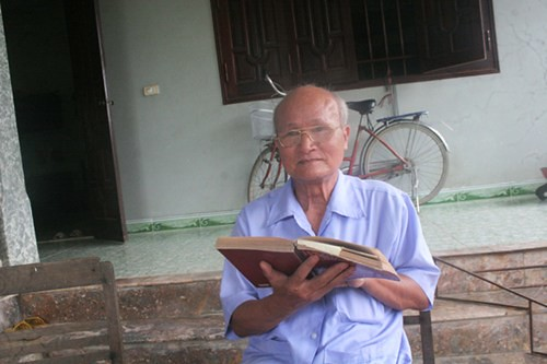 Một cụ cao niên giở các trang sách sử, tự hào kể về ngôn ngữ làng Đa Chất