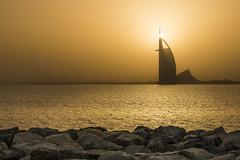 Burj Sunrise (ecmguy77) Tags: dubai burj burjalarab burjkhalifa sunrise haze yellow orange rocks ocean water uae ecmguy robertwork