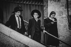 A Hasidic Jewish man wears a fur hat and bekishe leads young boys along a walkway in the Old City of Jerusalem (Alexandra Lande) Tags: old city boy sky man black students hat stairs fur israel palestine jerusalem cap jew locks conservative railing yarmulke hasidim bekishe kippeh