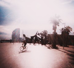 Promenade (teaselbrush) Tags: shot film camera toy superheadz slim white angel widescreen wide angle glitch blur photography barcelona spain urban city sun beach seafront promenade sea ocean vignetting light leak shadow silhouette sculpture modern statue geometric angles shapes bicycle cyclist palm tree