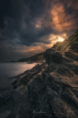 Stormy Golden Eye (Manuel.Martin_72) Tags: sunset sea summer italy storm clouds evening nikon rocks gloomy darkness cloudy stones dramatic it thunderstorm dramaticsky waterreflections lacona coloredsky d810 manuelmartin wwwmanuelmartinphotographycom