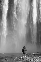 Skogafoss (Claire Willans) Tags: portrait people blackandwhite cliff nature water monochrome river waterfall iceland power small lone awe skogafoss inawe