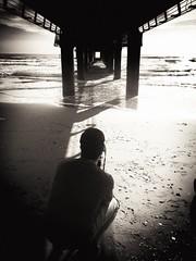 Studying the waves (elisabartolini) Tags: sunset sea blackandwhite bw italy seascape man love beach water monochrome architecture landscape pier seaside sand waves photographer shadows darkness tuscany pillars bnw versilia takingpictures onde iphone pontile blackwhitephotography underthepier waveporn iphone6