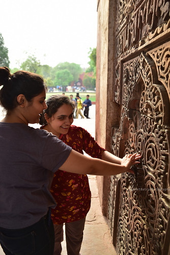 Accessible Tour of Red Fort, New Delhi: Ambika, a young blind girl trying to understand the kaarigari on the walls of the fort, by touching the designs.