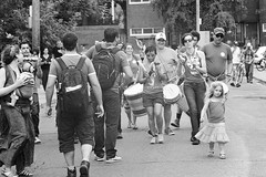 Sassy and Samba (Georgie_grrl) Tags: pedestriansunday july2016 social community music buskers performers musicians pentaxk1000 takumar125135mm toronto ontario kensingtonmarket candids blackandwhite whome ilford400 samba band percussion group drums girl child tude cute sassy strut