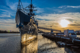 The USS Barry destroyer at the Washington Navy Yard reflects in the Anacostia River at sunset