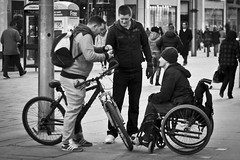 Deals On Wheels (Leanne Boulton) Tags: life lighting street city uk light shadow people urban blackandwhite bw white man black detail men texture monochrome bike bicycle youth canon landscape photography 50mm mono scotland living blackwhite natural humanity outdoor glasgow candid wheelchair wheels group young streetphotography social scene human shade 7d society depth tone candidstreetphotography