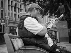 Whats in the paper today (Nikonsnapper) Tags: street 2 man monochrome bench reading newspaper cardiff olympus unposed zuiko omd em1 1240mm photingo