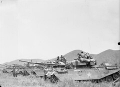 Centurion tanks of the 8th King's Royal Irish Hussars wait with troops of the 1st Commonwealth Division to cross a pontoon bridge over the Imjin River.