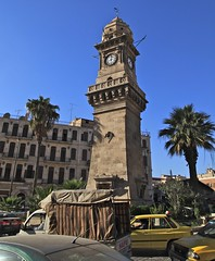 Clock Tower Aleppo The Ancient City That Was Nov 1 2010 Syria Middle East (eriagn) Tags: travel art history tourism wool rock fruit architecture concrete religious photography wooden traffic citadel minaret traditional prayer religion middleeast streetphotography documentary mosque tourist tourists unescoworldheritagesite traveller textures syria souk historical produce bazaar dailylife textiles fortification moat fortress weaving income citizens aleppo hawkers syrian bathhouse suq shopkeeper marked beliefs ngaire mosqueinterior ancientcity umayyadmosque orientalrugs camelhair medievalbuilding ceilingdecoration oldwalledcity citadelofaleppo traditionaltextiles eriagn ngairehart almadinasouq syrianstreetfood syrianpostbox
