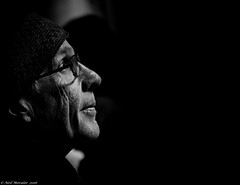 Amazed. (Neil. Moralee) Tags: old light shadow portrait people blackandwhite bw white toronto canada man black male monochrome face hat blackbackground contrast dark mono glasses amazing nikon close zoom candid low neil mature stare wrinkled 18300mm d7100 moralee neilmoralee canadaneilmoraleenikond7100