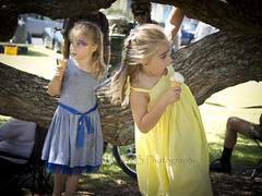 Ava and Chloe 2 (ArdieBeaPhotography) Tags: park family blue friends tree girl yellow tongue sisters portraits children child dress branches sunny fair lick icecream pohutukawa