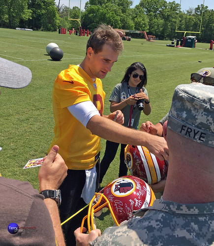 Redskins QB Kirk Cousins signs autographs on opening day of OTAs for the military.