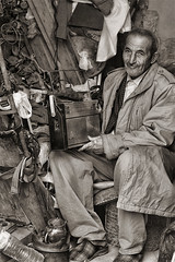 An Ancient Radio Repairman Black And White (Bouquet of arts) Tags: radio tunisia oldman medina worker oriental sousse oldcity blackandwhitephotography repairman arabicman radiorepairman