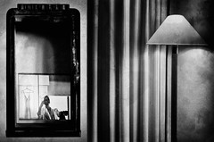 """Nocturne"" (helmet13) Tags: bw woman night movie mirror tv curtain nocturne hotelroom floorlamp aoi 200faves peaceaward heartaward leicaxvario"