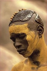 Sudan. A Nuba from Kau with his painted face mask, featured in the 1976 publication: People of Kau. // by   Leni Riefenstahl (mike catalonian) Tags: africa portrait color male face photography sudan 1970s 1976 nuba kau northernregion leniriefensthal