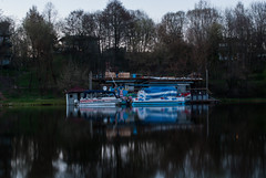 Boat (modestmoze) Tags: blue trees red sky brown white house reflection green nature wet water grass yellow architecture buildings river grey lights boat wooden day branches hill floating deck flowing lithuania vilnius wunning