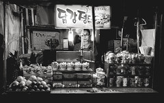 Low Key Local (TheLostLens.co.uk) Tags: street travel people blackandwhite woman chicken monochrome asian asia market candid streetphotography korea korean busan vendor southkorea streetfood rok environmentalportrait middleaged nampodong gyeongsangnamdo southgyeongsangprovice