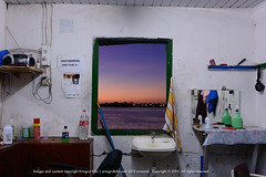 Sunrise (Ertugrul Kilic) Tags: street sunset people color colour reflection window nature public radio sunrise mirror nikon mess bottles availablelight saturday award towel professional barbershop barber sur ipa awards unposed perfumes broom countertop broomstick whitewall brokenwindow cassetteplayer suriname awardwinningphoto paramaribo viewfromwindow spraybottle throughwindow 2470mm babypowder noglass 2ndplace internationalphotographyawards surinameriver whitesink kilic ertugrul d2xs nonaltered nikond2xs greenframe windowwithoutglass glasslesswindow talcpowder sunsetinwindow nikkor2470mmf28gedafs ipa2009 ertugrulkilic 5thdecember2009 awardwinningsunset availableforlargeprint awardwinningsunrise greenframewindow messybarbershop noglasswindow sunriseinwindow woodengreenframe