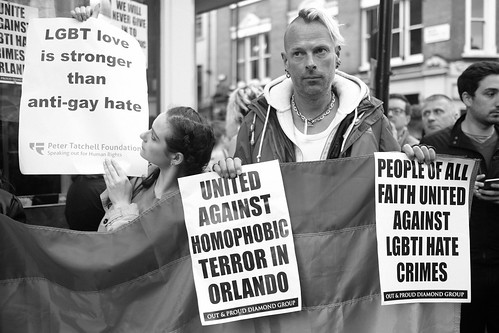 LGTB love is stronger than anti-gay hate - Two activists carrying placards during London's vigil in memory of the victims of Orlando's gay nightclub terror attack.