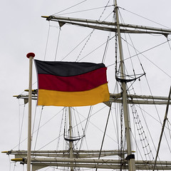Flag of Germany against the background of the system of ropes and  sails (zivko.trikic) Tags: flag cruise mode germany nautical deutschlanddeck cloud travel day ropes sign culture symbol yachting ship old obsolete yacht woods traditional rigger masts rigging equipment transport tall sailboat up high blue outdoors transportation backgrounds sky boat antique sea sail part angle water journey vessel