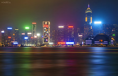 Hong Kong by Night (Ben Heine) Tags: china city longexposure blue sea blur reflection water colors skyline composition canon buildings river painting photography hongkong lights colorful asia cityscape skyscrapers purple harbour lumière posters huge blocks editing lightshow retouching ville waterscape harbourcity colorés sonetlumière artprints megapole photoprints hongkonglandscape bytheharbour canonmarkii benheineart buyhongkongposters