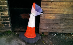 the cone of shame (dr_loplop) Tags: road street door wood orange pet black brick grass wall fence neck weeds traffic panel cone pavement timber thing board device reflective groove collar elizabethan obligatory velcro scratch anti plank brickwork cladding slat wonk coneporn