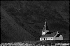 Vik i Myrdal Church (John Fÿn Photography) Tags: shadow blackandwhite bw foothills mountain mountains church monochrome sunshine landscape grey mono is iceland high nikon cross outdoor south hill gray peak steeple vik hills ridge nordic nikkor elevation stark alp 70200 vík crag blackroof 70200mmf28 d810 nikon70200mm republicoficeland niksoftware nikonfx silverefex silverefexpro