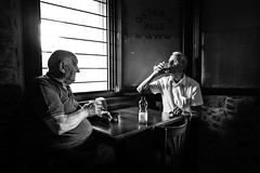 Two friends and the window light in osteria (Giulio Magnifico) Tags: beauty 28mm lightning feletto tradition udine wine osteria blackwhite emotions friuli beautiful window wood bw old powerful italy drink classic typical rural candid leicaq reportage smile stones light leica soul soulful summilux life mood
