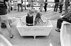 Waiting for Launch (F. Neil S.) Tags: girls slr film monochrome 35mm blackwhite wooden waiting waterfront contest negative scanned rowboat seated boatbuilding xtol nikonf6 blancetnoir selfdev nikonls4000 kentmere400 beaufortdocks