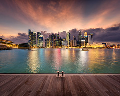 Boundless (Scintt) Tags: city travel light sunset sky urban panorama sun water skyline architecture modern clouds marina buildings reflections photography evening bay hall wooden jon singapore downtown glow cityscape colours place skyscrapers pano board platform structures surreal anchor boardwalk cbd rays sands chiang epic stitched mbs raffles pagar tanjong scintillation scintt