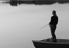 A girl fishing (Antti Tassberg) Tags: sunset summer people blackandwhite bw sun lake monochrome espoo lens landscape prime boat fisherman sundown fisher 135mm vene jrvi auringonlasku aurinko pitkjrvi kalastaja laaksolahti