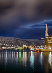 Tromso Harbour by Night (Nigel Jones QGPP) Tags: mountain reflection tower water norway lights cathedral harbour flag arcticcircle tromso