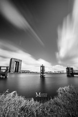 The pole (Maarten Mensink) Tags: longexposure blackandwhite bw white black water grass lines clouds reflections streaks ultrawideangle weldingglass