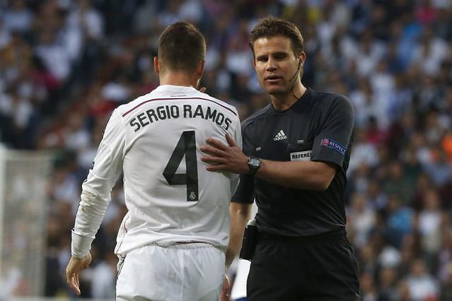El árbitro alemán Felix Brych junto al defensa del Real Madrid Sergio Ramos durante el partido de vuelta de cuartos de final de la Liga de Campeones que el Real Madrid y el Atlético de Madrid disputan esta tarde en el estadio Santiago Bernabéu, en Madrid.