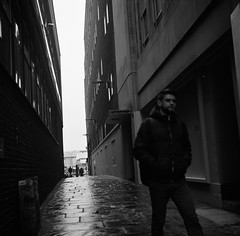 Back alley.. (Charles the Power) Tags: road lighting street uk trees england people urban blackandwhite white black london 120 film monochrome contrast buildings reflections mono outfit exposure locals shadows angle outdoor walk candid expressions hats documentary silhouettes angles surreal objects railway journey portraiture rails hp5 medium format experimentation highstreet passerby atmospheric composistion filmisnotdead ilfords