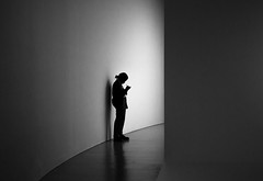 Silhouette of a Museum Guard (John Bense) Tags: light shadow blackandwhite monochrome lines silhouette wall museum standing writing washingtondc hall guard hallway walls hirshhorn hirshhornmuseum