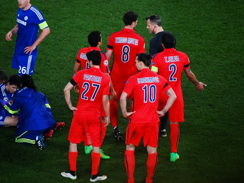 The referee Bjorn Kuipers resists the protests of Paris Saint-Germain's Thiago Motta, Marquinhos, Thiago Silva, Javier Pastore and Zlatan Ibrahimovic as Oscar of Chelsea recovers on the ground