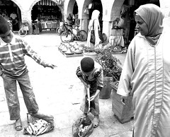 'How Much Is The Fish, Boys?' Moroccan Portraits by Elena Savonicheva, 2015 (elenasavonicheva) Tags: africa street travel boy blackandwhite woman fish boys childhood yard children photography photo blackwhite fisherman day commerce child market streetphotography morocco maroc medina streetphoto marketplace trade salesmen seller essaouira moroccan sellers blackwhitephoto blackandwhitephoto travelphotography travelphoto jellaba travelpics moroccans travelpic