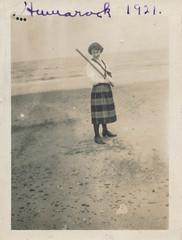 Woman stands on a beach holding a stick (simpleinsomnia) Tags: old woman white black beach monochrome scarf vintage found blackwhite baseball antique snapshot bat photograph vernacular stick foundphotograph