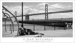 Reclining Man, San Francisco Bay (G Dan Mitchell) Tags: sanfrancisco california street bridge urban blackandwhite usa man monochrome america fence bay north sidewalk embarcadero rest reclining