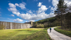 Cyclist at Derwent dam (Keartona) Tags: road morning england sky panorama tourism clouds spring cyclist path dam derwent derbyshire peakdistrict fluffy sunny reservoir valley overflowing
