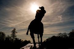 what the sun's hidden / Lo que se oculta del sol (Luis DLF) Tags: uk blue sunset red sky sculpture horse cloud sun men london statue canon explore hide hydepark siluete