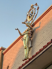 Sculpture of a woman on the roof of a building. (dckellyphoto) Tags: woman nude statue sculpture weathervane windmill gold ball pose holding roof mounted brick winstonsalem tradestreet decorative female northcarolina winstonsalemnc winstonsalemnorthcarolina 2016 sunset warmlight
