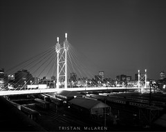 Nelson Mandela Bridge, BW (Tristan McLaren) Tags: africa road lighting street city longexposure bridge light two people urban bw white building tower heritage film tourism monochrome station skyline architecture tristan night train landscape southafrica photography lights evening blackwhite office construction cityscape photographer exterior traffic bright engineering places nelson landmark structure architectural mclaren commercial infrastructure historical 4x5 format cbd column tall newtown sculptural johannesburg largeformat structural mandela lightstreak viewcamera gauteng artificiallighting linhoftechnika 90mmschneidersuperangulon