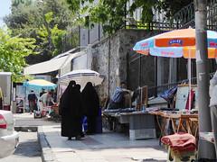 Three women & three umbrellas on a street in Istanbul (ashabot) Tags: street turkey markets hijab cities istanbul streetscenes peopleonthestreet peopleoftheworld carsaf