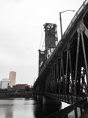Steel Across The Water (TMimages PDX) Tags: street city bridge people urban water monochrome skyline buildings river portland geotagged photography photo waterfront image streetphotography streetscene explore photograph pacificnorthwest vignette span fineartphotography iphoneography