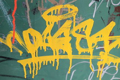 Yellow Graffiti on Green Mailbox